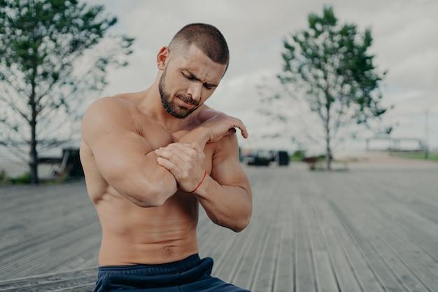 Bel homme musclé avec torse nu à l'extérieur faisant de l'exercice de remise en forme