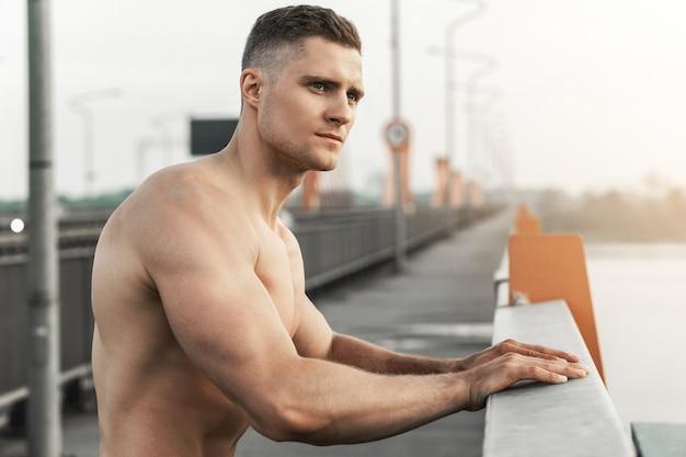 Bel homme musclé avec torse nu pendant l'entraînement de remise en forme sur un pont