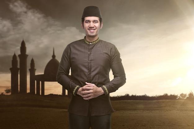 Bel homme musulman asiatique debout pendant le coucher du soleil