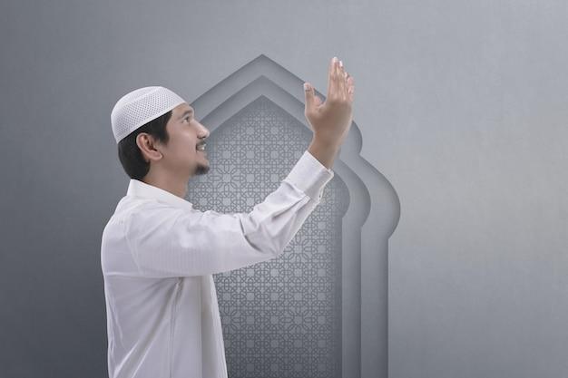Bel homme musulman asiatique, levant la main et prier