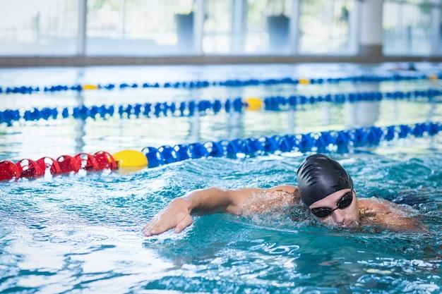 Bel homme nageant dans la piscine