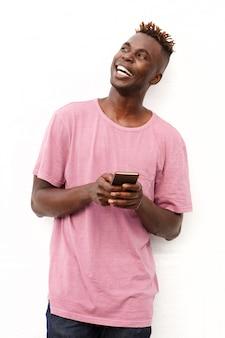 Bel homme noir avec un téléphone portable à la recherche de suite sur fond blanc