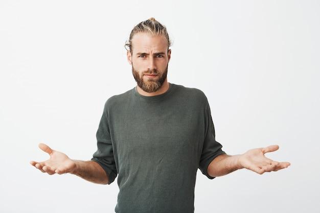 Bel homme nordique avec barbe et coiffure élégante écarte les mains avec une expression cynique et méchante