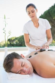 Bel homme obtenir un massage aux pierres chaudes au bord de la piscine