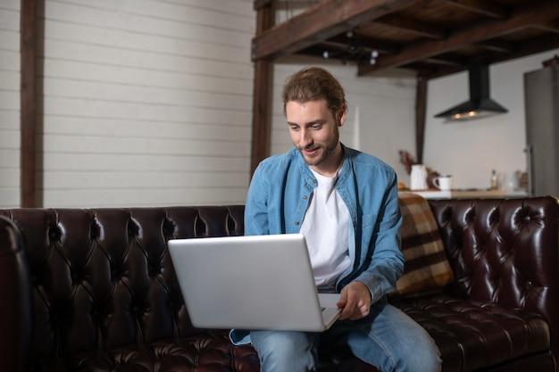 Un bel homme occupé à travailler avec l'ordinateur