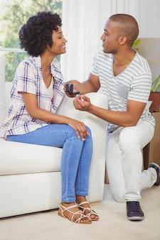Bel homme offrant une bague de fiançailles à sa petite amie dans le salon