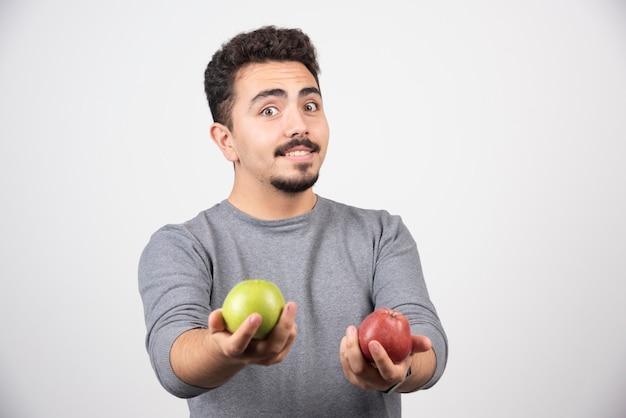 Bel homme offrant des pommes sur fond gris.
