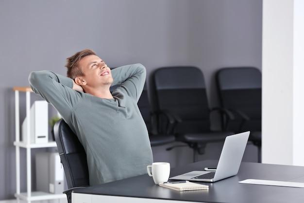 Bel homme avec ordinateur portable au bureau
