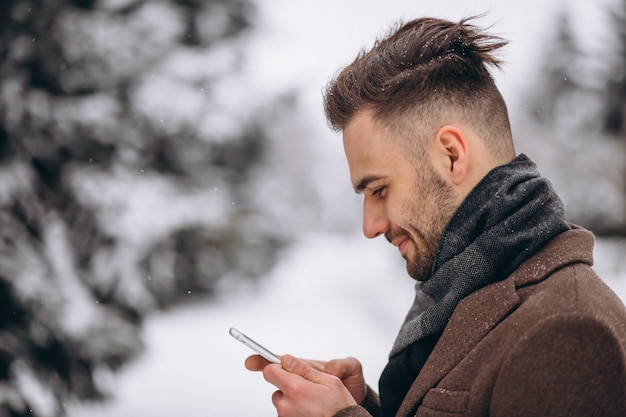 Bel homme parlant au téléphone dans un parc d'hiver