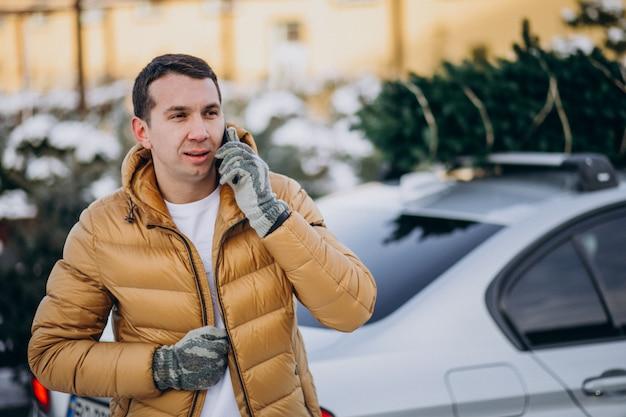 Bel homme parlant au téléphone par la voiture avec arbre de noël sur le dessus