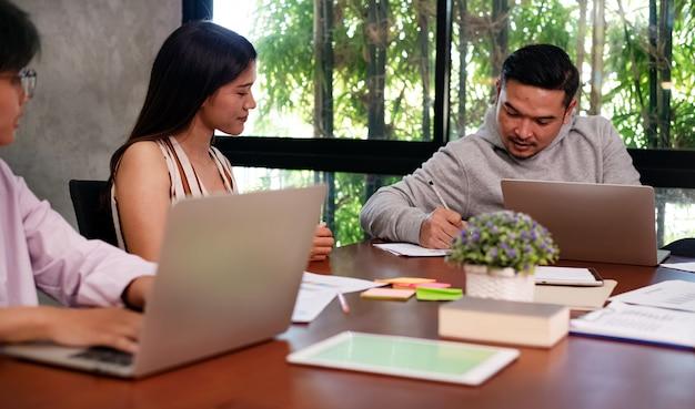 Bel homme parlant avec de jeunes gens d'affaires travaillant, avec une réunion d'équipe de collègues,