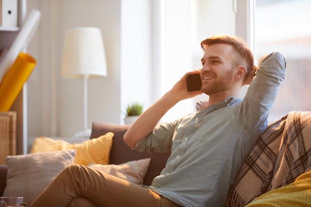 Bel homme parlant par téléphone à la maison