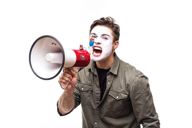Bel homme partisan fidèle fan de l'équipe nationale de la république de corée avec le visage du drapeau peint criant dans un mégaphone avec une main pointue. émotions des fans.