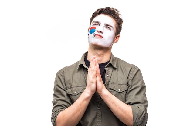 Bel homme partisan fidèle fan de l'équipe nationale de la république de corée avec le visage du drapeau peint prier sur blanc. émotions des fans.