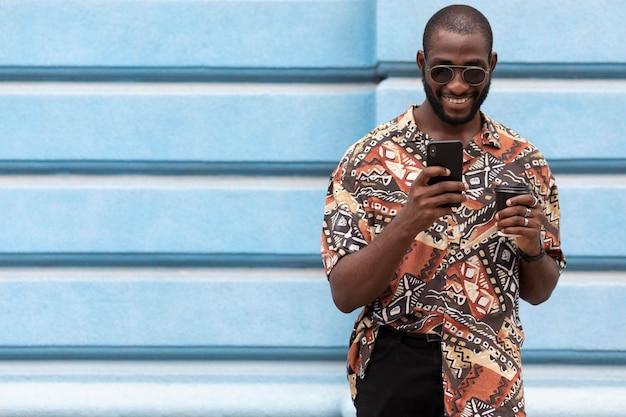 Bel homme passant du temps à l'extérieur et utilisant un smartphone moderne