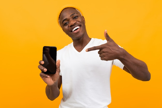 Bel homme à la peau foncée souriant dans un t-shirt blanc est titulaire d'un smartphone sur orange