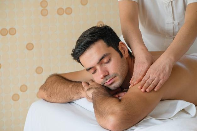 Bel homme pendant le massage aux huiles essentielles dans le spa de la chambre