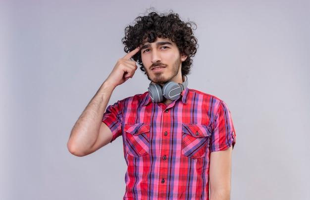 Un bel homme pensant aux cheveux bouclés en chemise à carreaux dans les écouteurs pointant sur la tête avec l'index