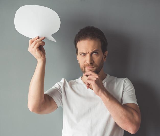 Bel homme pensif tient une bulle de dialogue.