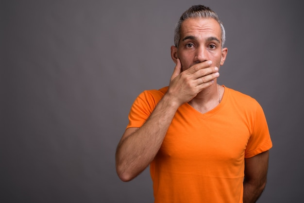 Bel homme persan aux cheveux gris portant un t-shirt orange