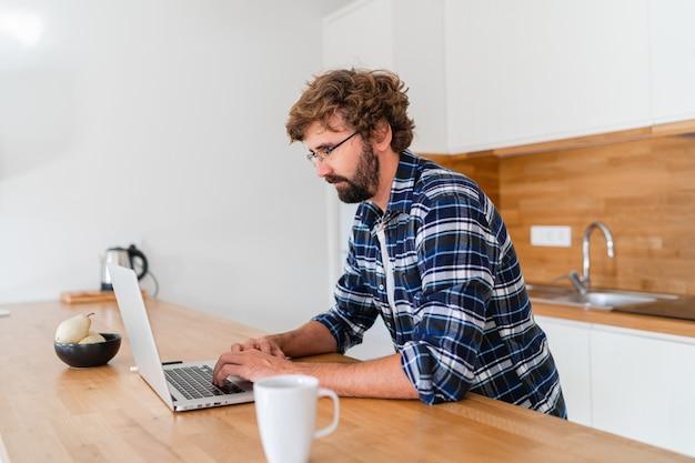 Bel homme pigiste utilisant un ordinateur portable étudiant le travail en ligne à domicile