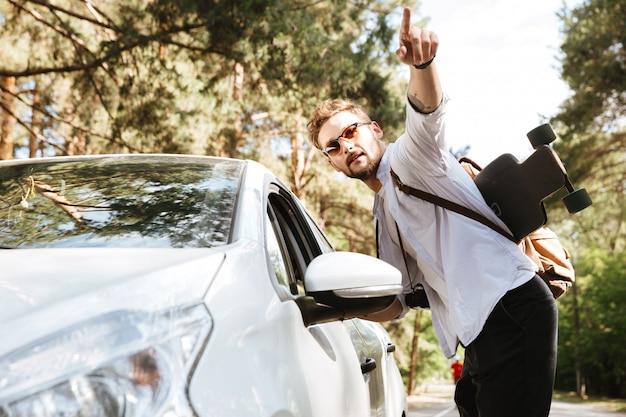 Bel homme avec planche à roulettes à l'extérieur debout près de voiture pointant.