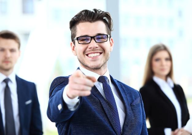 Bel homme pointant son doigt sur vous sur le fond des gens d'affaires