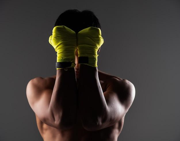 Le bel homme portant un gant jaune, met les mains pour fermer son visage, montre le poing, prépare le coup de poing