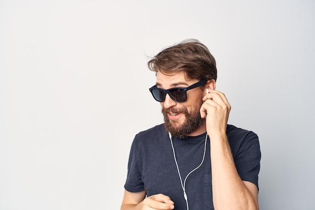 Bel homme portant des lunettes écoutant de la musique sur un casque isolé sur fond. photo de haute qualité