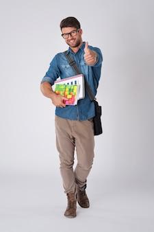 Bel homme portant des lunettes de mode et un chapeau de laine avec cahier et sac d'école