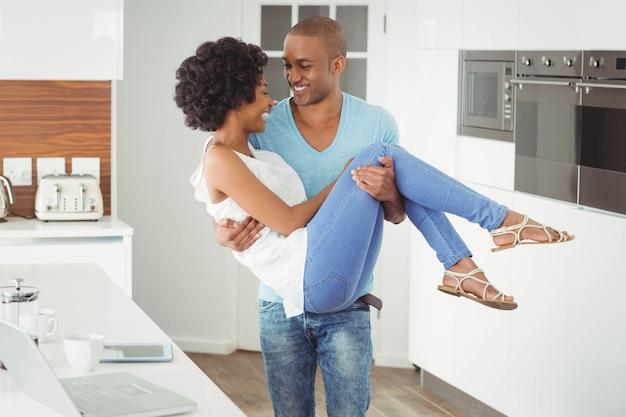 Bel homme portant sa petite amie dans la cuisine
