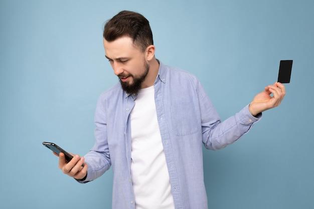 Bel homme portant des vêtements de tous les jours isolés sur un mur de fond tenant et utilisant un téléphone et une carte de crédit pour effectuer le paiement en regardant l'écran du smartphone