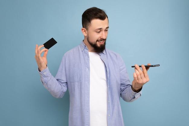 Bel homme portant des vêtements de tous les jours isolés sur le mur de fond tenant et utilisant le téléphone et le crédit