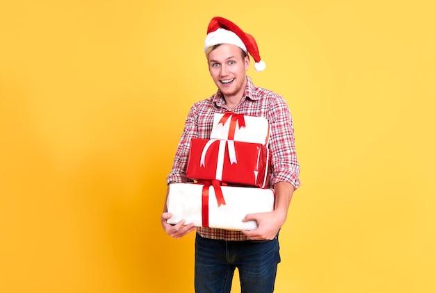 Bel homme porte bonnet de noel tenant beaucoup de boîte-cadeau sur fond jaune. concept de noël et bonne année.