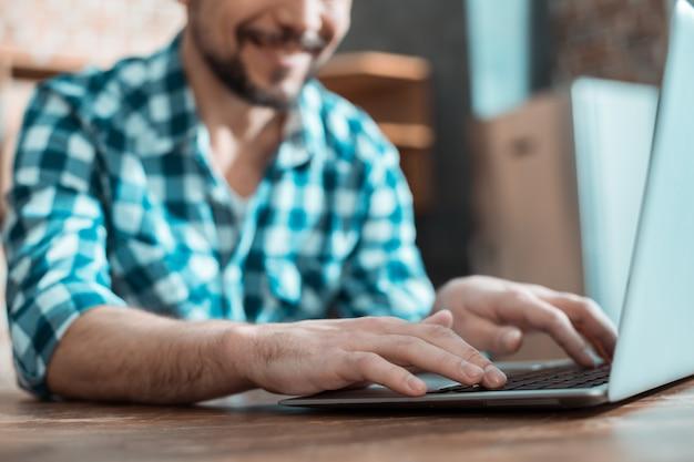 Bel homme positif intelligent assis à l'ordinateur portable et tapant tout en faisant son travail
