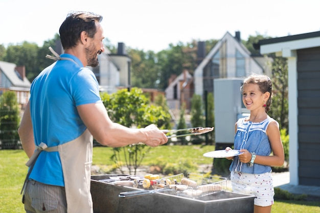 Bel homme positif regardant sa fille tout en mettant des saucisses dans son assiette