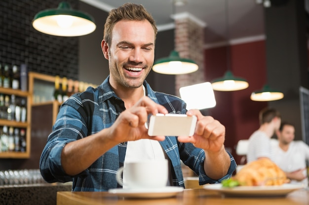 Bel homme prenant une photo de son sandwich
