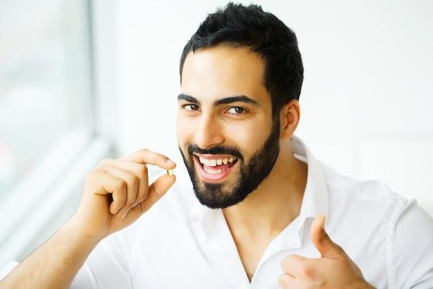 Bel homme prenant la pilule, médecine. vitamines et suppléments