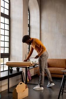 Bel homme prenant sa toile tout en étant dans son studio artistique