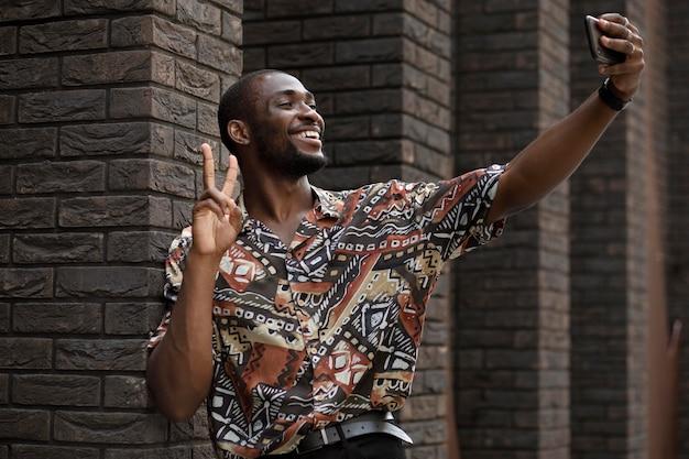 Bel homme prenant selfie avec un smartphone moderne à l'extérieur