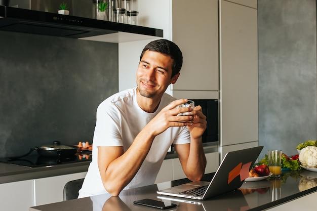 Bel homme prenant son petit déjeuner dans la cuisine avec ordinateur portable