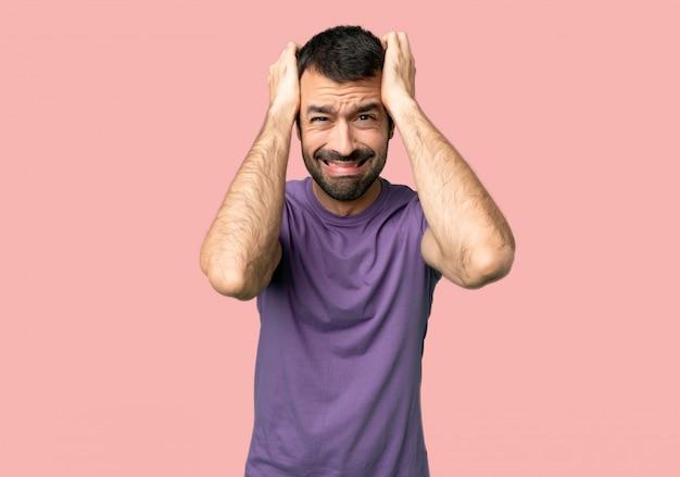 Bel homme prend les mains sur la tête car a la migraine sur fond rose isolé