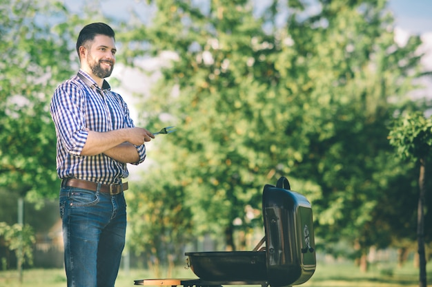 Bel homme prépare un barbecue pour les amis. homme, cuisson viande, sur, barbecue, -, chef, mettre, quelques, saucisses, et, pepperoni, sur, gril, dans parc, extérieur, -, de, manger, extérieur, pendant, heure d'été