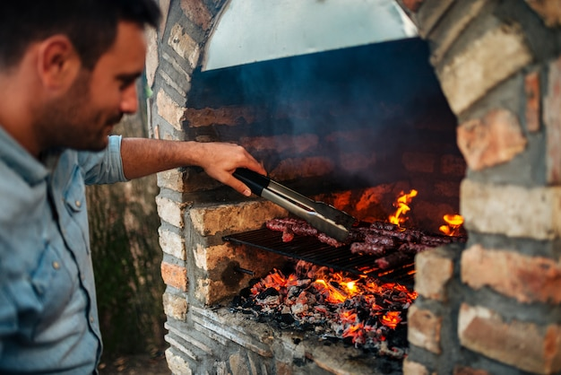 Bel homme prépare la viande sur le barbecue en briques façonné à l'ancienne.