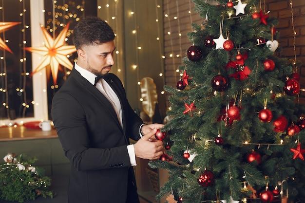 Bel homme près de l'arbre de noël. gentelman dans un costume noir.