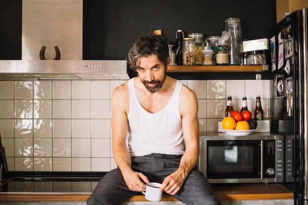 Bel homme provocant posant sur le comptoir