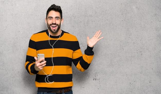 Bel homme avec pull rayé surpris et envoyant un message sur le mur texturé