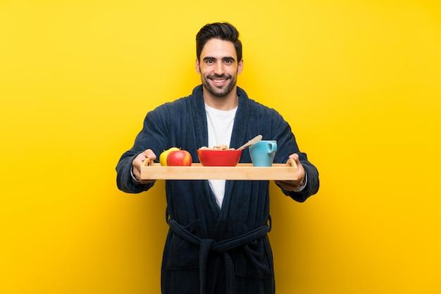 Bel homme en pyjama sur mur jaune isolé