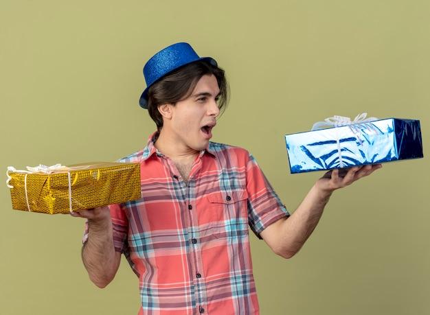 Bel homme de race blanche agacé portant un chapeau de fête bleu détient des coffrets cadeaux