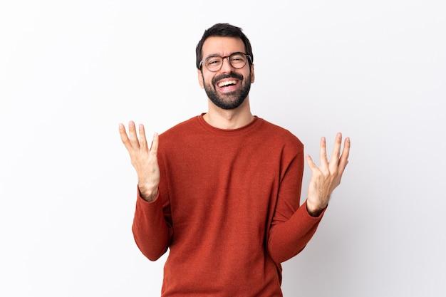 Bel homme de race blanche avec barbe sur mur blanc isolé souriant beaucoup